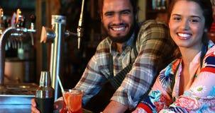 微笑的女服务员和男服务员画象有鸡尾酒搅拌器和鸡尾酒的在酒吧柜台