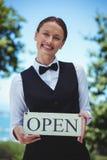 微笑的女服务员藏品打开标志 图库摄影