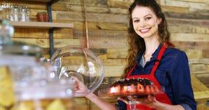 微笑的女服务员藏品蛋糕画象在柜台的 股票视频