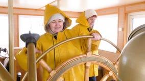 微笑的妇女上尉转动的方向盘浮动船 帆船在航海的指点舵的女性上尉 股票视频