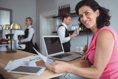 微笑的妇女与图表一起使用绘制和膝上型计算机在酒吧柜台 免版税库存照片