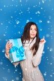 微笑的妇女举行蓝色礼物盒 圣诞节, x-mas,人们,幸福概念-愉快的妇女在冬天穿衣 免版税库存图片