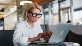 微笑的妇女企业主与在享受设备的舒适咖啡馆的膝上型计算机一起使用 股票视频