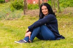 微笑的妇女休息在庭院里 免版税图库摄影