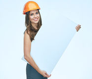 微笑的妇女佩带保护拿着白色banne的建造者盔甲 库存照片