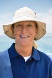 微笑的妇女佩带的帽子画象在游艇的 免版税库存照片