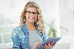 微笑的妇女佩带的镜片画象,当使用数字式片剂时 库存图片
