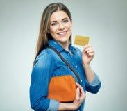 微笑的妇女偶然穿戴的展示金黄信用卡 免版税库存照片
