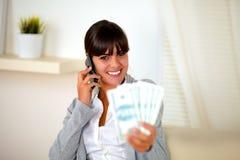 微笑的妇女发表演讲关于移动电话与货币 库存照片