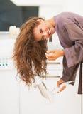 微笑的妇女吹干的头发在卫生间里 免版税图库摄影