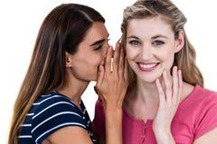 微笑的妇女告诉秘密对朋友,当站立时 免版税库存照片