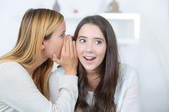微笑的妇女告诉秘密对朋友 免版税库存图片