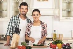 微笑的妇女和丈夫烹调与新鲜蔬菜 免版税库存图片