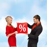 微笑的妇女和人有红色百分之销售的签字 库存图片