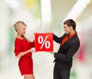 微笑的妇女和人有红色百分之销售的签字 图库摄影