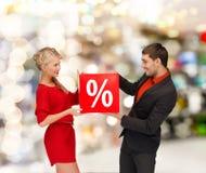 微笑的妇女和人有红色百分之销售的签字 库存照片