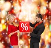 微笑的妇女和人有红色百分之销售的签字 免版税库存图片