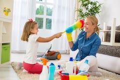 微笑的妇女和女儿享用到清洗的房子 免版税库存照片