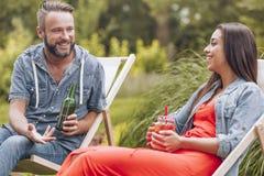 微笑的妇女和愉快的人饮用的啤酒和鸡尾酒,当放松在sunbeds时 免版税图库摄影