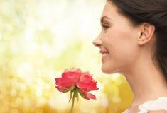 微笑的妇女嗅到的花 免版税库存照片