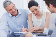 微笑的妇女在一contrat签字以她的在沙发的合作 免版税库存图片