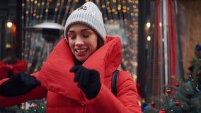 微笑的妇女在与圣诞节装饰的一个门前跳舞在一个老城市的街道上 股票视频