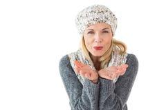 微笑的妇女在冬天塑造吹在照相机 图库摄影