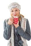 微笑的妇女在冬天塑造看与杯子的照相机 库存照片