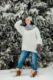微笑的妇女在冬天穿戴了在深雪的温暖的身分 免版税库存图片