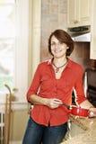 微笑的妇女在厨房里在家 免版税库存照片