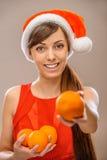 微笑的妇女在圣诞老人衣裳用桔子 库存图片