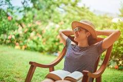 微笑的妇女在夏天晴朗的背景中 免版税库存照片