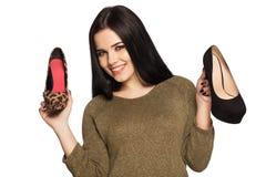 微笑的妇女在她的手上的拿着两双鞋子 免版税库存图片