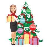 微笑的妇女在手上的拿着一件礼物在圣诞树的背景 免版税库存照片