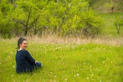 微笑的妇女在春天草坐 库存图片