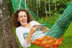 年轻微笑的妇女在有片剂个人计算机的吊床在 免版税图库摄影