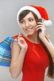 微笑的妇女在有电话的圣诞老人衣裳 图库摄影