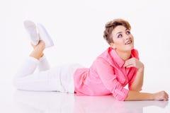 微笑的妇女在桃红色衬衣和看的地板放置楼上 免版税库存图片