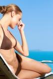 微笑的妇女在海滩睡椅的布朗比基尼泳装 免版税库存图片