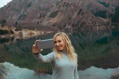 微笑的妇女在湖做selfie 免版税图库摄影