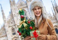 微笑的妇女在米兰,有圣诞树和礼物的意大利 图库摄影