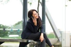 微笑的妇女在谈话的公共汽车站坐手机 免版税库存图片
