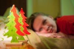 年轻微笑的妇女在Xmas树玩具看见 图库摄影