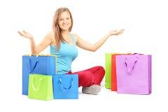 年轻微笑的妇女坐与许多购物袋a的一个地板 免版税库存照片