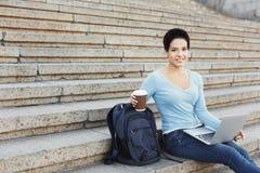 微笑的妇女坐台阶使用膝上型计算机 免版税库存照片