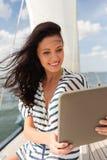 微笑的妇女坐有片剂个人计算机的游艇 免版税图库摄影