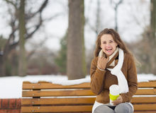 微笑的妇女坐长凳在冬天户外 免版税库存图片