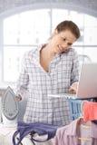 微笑的妇女多任务家事和膝上型计算机 免版税库存图片