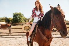 微笑的妇女女牛仔骑乘马在村庄 免版税库存照片