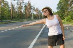 微笑的妇女室外画象站立在路的帽子的停止汽车,拷贝空间 免版税库存照片